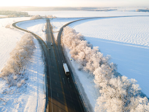 Lorry truck on the road surrounded by winter forest. Aerial view