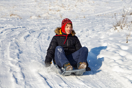 boy sliding down snow hill on sled outdoors in winter, sledging and season concept