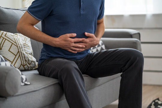 Stomach ache, man with abdominal pain suffering at home