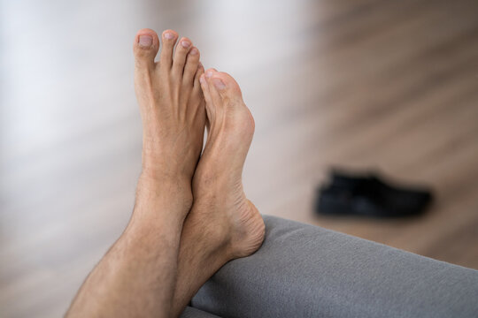 Tired man resting after work at home, male feet, body care concept