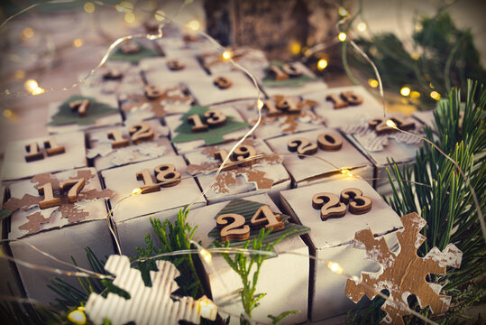 Self made christmas advent calendar in vintage style. Lying cubes in form of a christmas tree with fairy lights. Close-up with short depth of field.