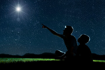 Obraz dad and son sit on the grass at night and look at the night sky - fototapety do salonu