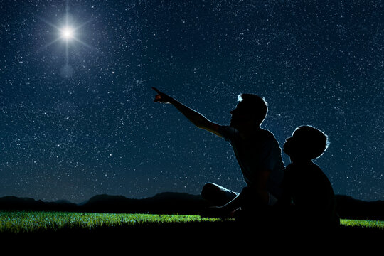 dad and son sit on the grass at night and look at the night sky