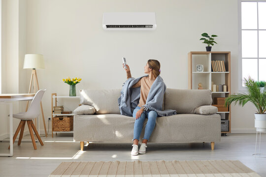 Woman who's sitting on sofa under warm plaid in living room switches off her air conditioner on wall. Young girl adjusting modern AC system, regulating temperature and enjoying cool fresh air at home