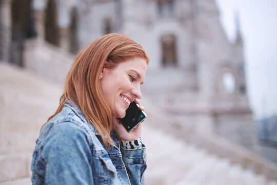 Happy young positive redhead woman calling in city