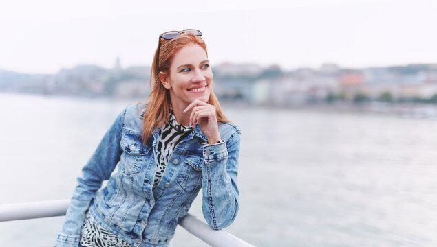 Happy young redhead woman looking away at riverbank