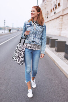 Fashionable young woman in blue jeans walking on street