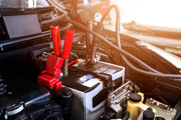Obraz car repair concept. closeup charging car battery with electricity through jumper cables with soft-focus and over light in the background - fototapety do salonu