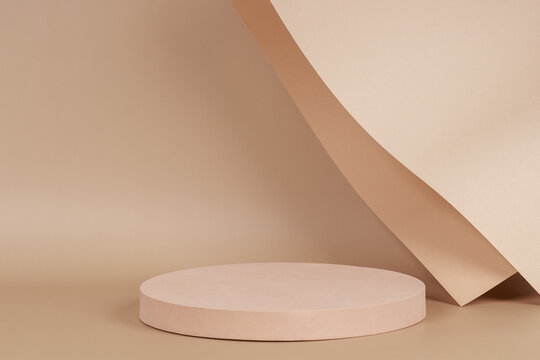 Abstract trendy composition with empty round podium platform for product presentation and curve shaped paper on pastel beige background. Front view