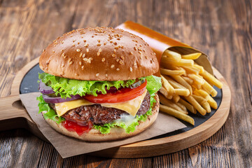 Obraz Delicious burger with  potato fries on a wooden table with a dark brown background behind. Fast food concept. - fototapety do salonu