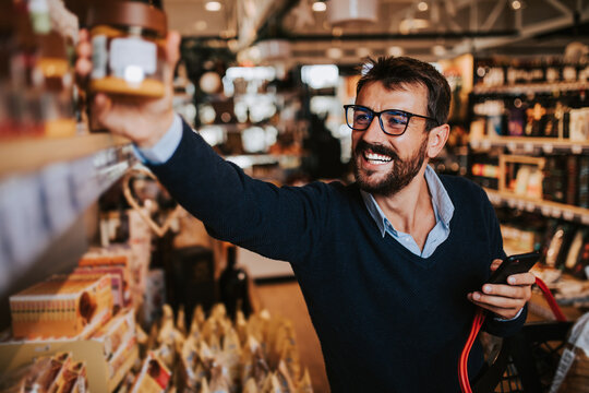 Handsome middle age man buying some healthy food and drink in modern supermarket or grocery store. Lifestyle and consumerism concept.