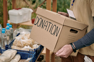 Obraz Male volunteer holding packed donation box while standing by table with free food - fototapety do salonu