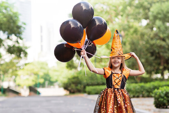 Lifestyle portrait of Happy Little caucasian Girl with blonde hair seven years old in black orange costume of which celebrating Halloween alone outdoor during Coronavirus covid-19 pandemic quarantine.