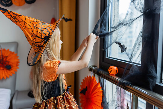 Little Girl in costume of which in decorated bedroom at home. Happy Halloween concept