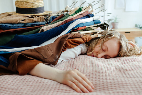 Woman with pile of clothes on bed