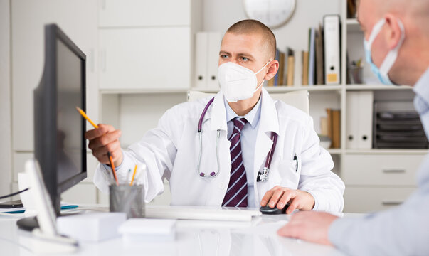 Doctor therapist male in face mask shows the patient the results of his tests and prescribes treatment in a modern office in the hospital