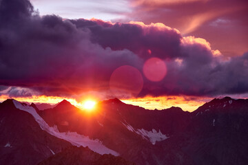 Sunset in mountains. Reflection of red sun on mountain snow peaks and clouds. Altai, Belukha area