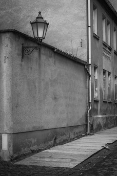 black and white photo of a street in need of renovation with damaged sidewalk and facades with a dilapidated old street lamp