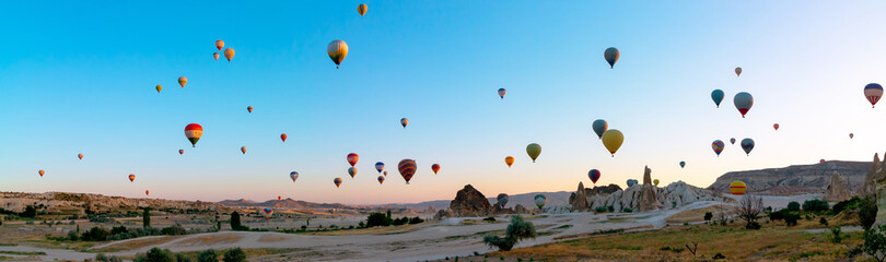 Panoramic view of Cappadocia with lots of hot air balloons on the air