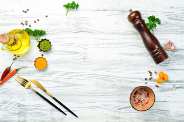 Obraz Cutlery, spices and vegetables on a white wooden background. Restaurant menu. Top view. - fototapety do salonu