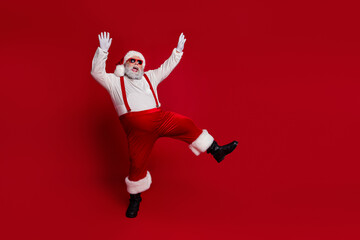 Photo of funny crazy santa claus wear red costume dark eyewear dancing celebrating noel isolated red color background