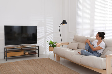 Obraz Woman watching television at home. Living room interior with TV on stand - fototapety do salonu