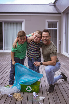 Portrait of caucasian father and two sons collecting plastic materials in a bag outdoors
