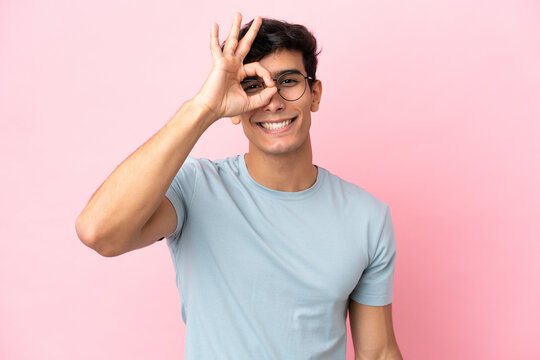Young Argentinian man isolated on pink background With glasses with happy expression