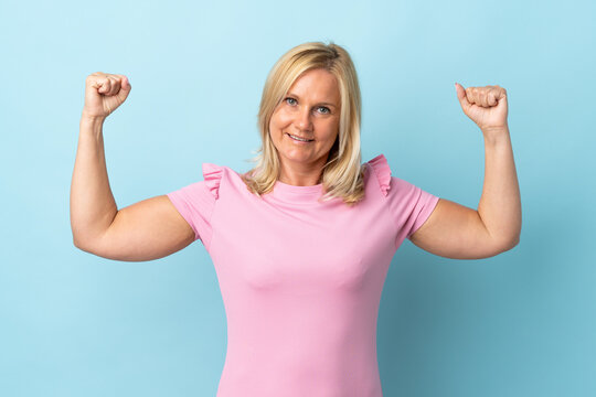 Middle age woman isolated on blue background doing strong gesture