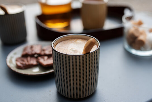 Coffee cream in a modern ceramic cup on a gray table in a cafe. Close-up with blurred background.