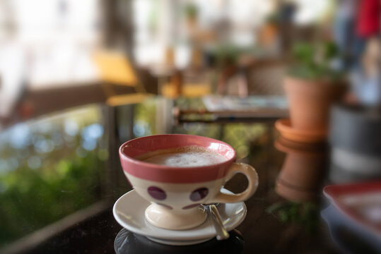 Coffee cream in a colorful ceramic cup on a glass table in a cafe. Close up with blurred background and space for text.