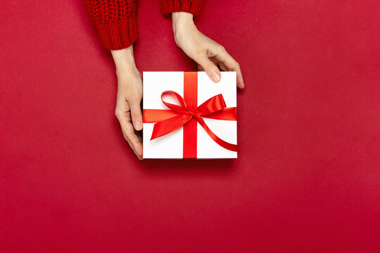 Christmas giving concept, top-down view of hands holding a gift box decorated with a red bow