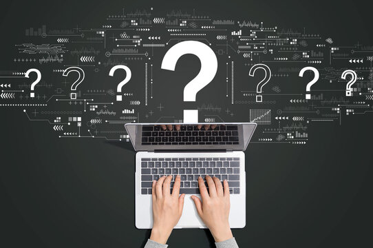 Question marks with person using a laptop computer