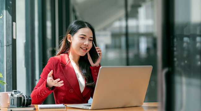 Young female entrepreneur using phone and laptop computer.