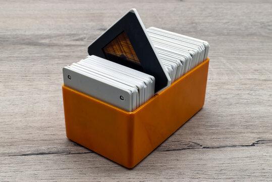 Old slides in a plastic box. Vintage 35mm slide film on wooden table.
