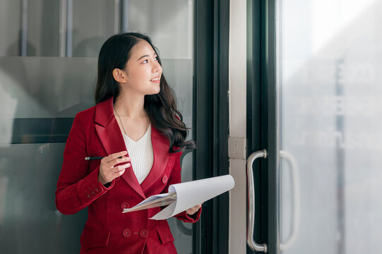 Young woman standing in office, smiling and looking outside.