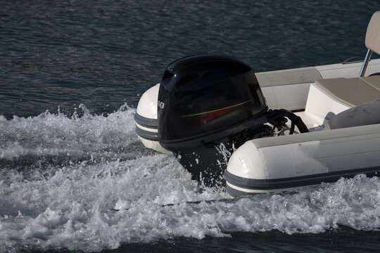 Zodiac outboat motor engine propeller while running on the blue sea