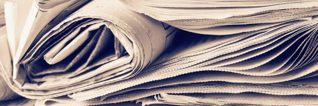 Panoramic image of old newspapers. Blur, selective focus. Media concept.