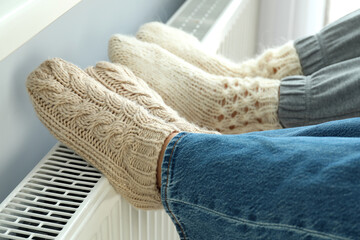 Obraz Concept of heating season with legs in knitted boots on radiator - fototapety do salonu