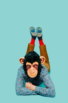 man wearing a monkey mask lying face down