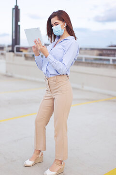 Young businesswoman in mask using tablet outdoor full body