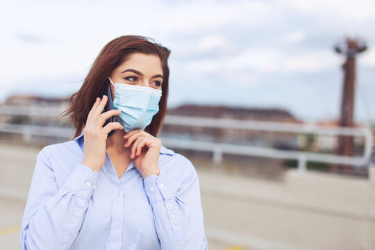 Young Caucasian businesswoman in mask calling  outdoors