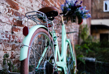 City bike near a brick wall. Bike with a bouquet in a basket. Bike leaning against the wall.