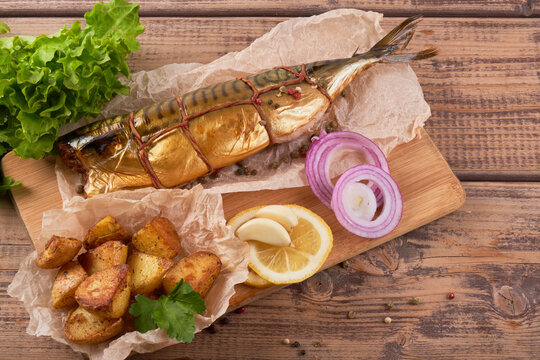 Composition smoked mackerel fish with garnish potatoes lemon greens onions served on wooden board plate top view