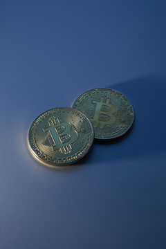 Two golden bitcoins isolated on blue background close-up with copy space, concept of growth and fall of cryptocurrency