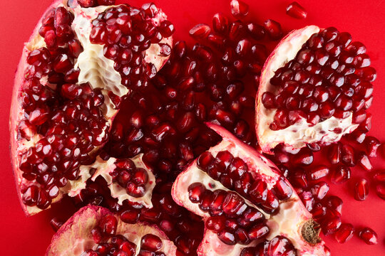 Ruby ripe fresh juicy sliced pomegranate isolated on red background