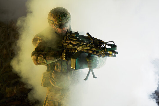 Portrait of airsoft player in professional equipment with machine gun in abandoned ruined building. Soldier with weapons at war in smoke and fog