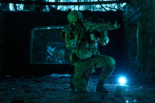 Portrait of airsoft player in professional equipment with machine gun in abandoned ruined building. Soldier with weapons at war