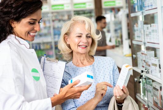 Pharmacist selling medications to senior female customer in the pharmacy store.