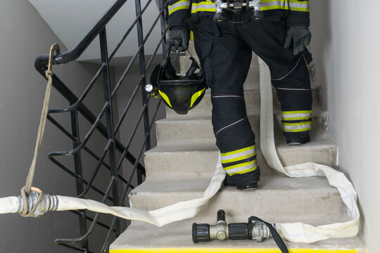 on a smoke-free staircase, a firefighter holds a helmet with a flashlight in his hands, against the background of special equipment a barrel and a hose for water supply